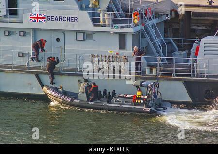 Newcastle, United Kingdom - October 5th, 2014 - UK border force officers boarding a RIB patrol boat alongside the - Stock Photo