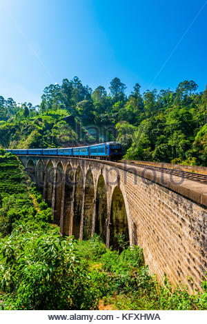 The Highland Express passes over the Nine Arch Bridge, Demodara, Ambagollapathana near Ella, Uva Province, Sri Lanka. - Stock Photo
