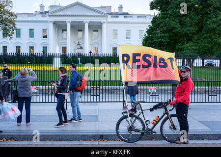 Anti-Trump resistance protester in front of the White House holding a Resist banner/flag, protesting against president - Stock Photo