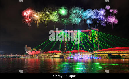 beautiful firework over Singapore city at night with laser show in marina bay water front - Stock Photo