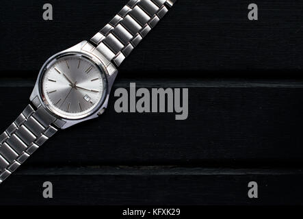 Stainless steel silver mens wrist watch on a black wooden surface, with lots of copy space and contrast - Stock Photo