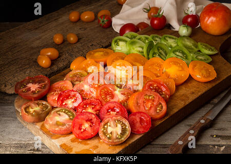 Various different color organic homegrown tomatoes on board. Cut red, yellow, orange and green tomato. Healthy vegetarian - Stock Photo