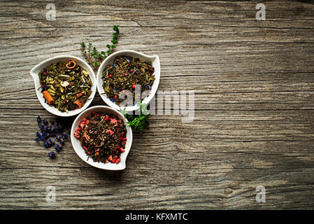 Dry tea collection of different types on wooden background - Stock Photo