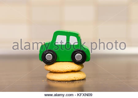 Green wooden toy car on two fresh biscuits on a wooden table - Stock Photo
