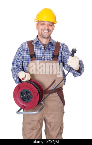 Happy Electrician Holding Wire Plug On White Background - Stock Photo