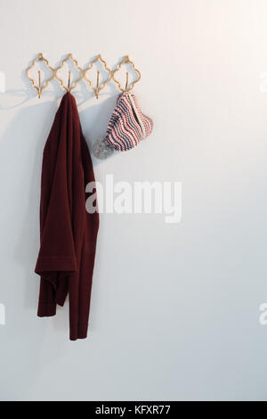 Warm clothes hanging on hook against white wall - Stock Photo