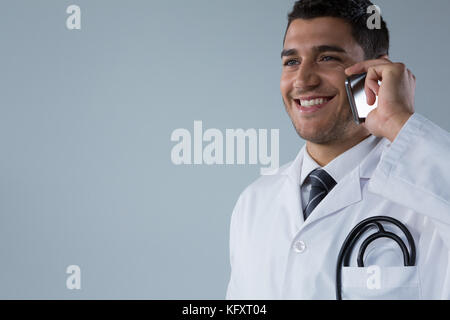 Close-up of smiling doctor talking on the mobile phone - Stock Photo