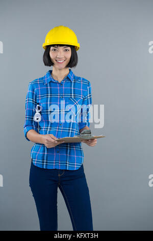 Portrait of smiling female architect holding clipboard and blueprint against grey background - Stock Photo