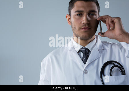 Close-up of doctor talking on the mobile phone against white background - Stock Photo