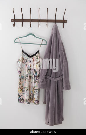 Bathrobe and nightwear hanging on hook against white wall - Stock Photo