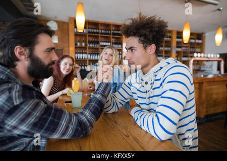 Confident two men arm wrestling in bar - Stock Photo