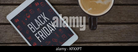 Digital tablet and cup of coffee on wooden plank against black friday advertisement - Stock Photo