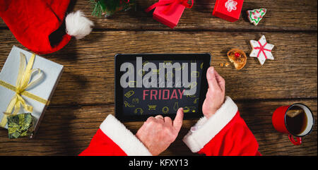 Black Friday with icons on blackboard against santa claus using digital tablet on table - Stock Photo