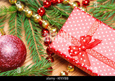 Christmas and New Year bright festive composition. Close-up of gift box with bow, spruce branches and Christmas - Stock Photo