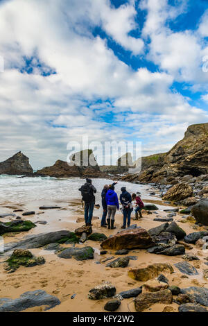 People watch as a Coastguard helicopter swoops and hovers around Bedruthen Steps in Cornwall, UK - Stock Photo