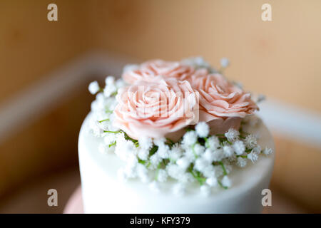 Close up of a pink icing fondant rose petals with babies breath decoration on top of a beautiful wedding cake in - Stock Photo