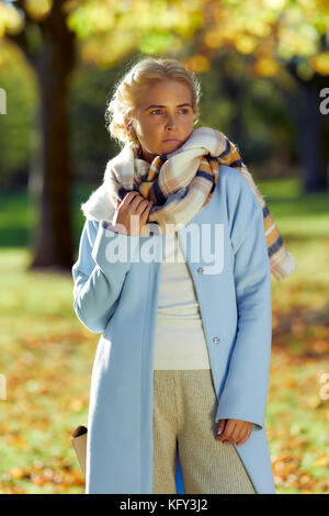 Woman looking concerned outdoors - Stock Photo