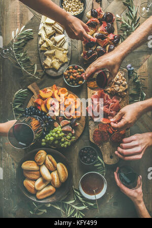 Flat-lay of friends hands eating and drinking together - Stock Photo