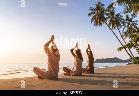 Group of three people practicing yoga lotus position on the beach for relaxation and wellbeing, warm tropical summer - Stock Photo
