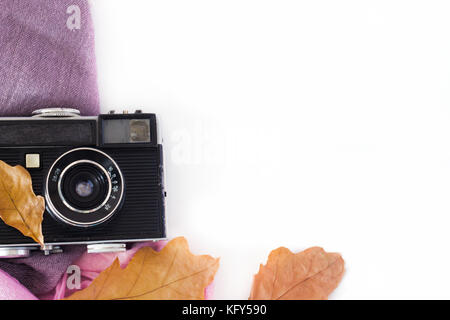 Vintage camera on white background and autumn leaves. - Stock Photo