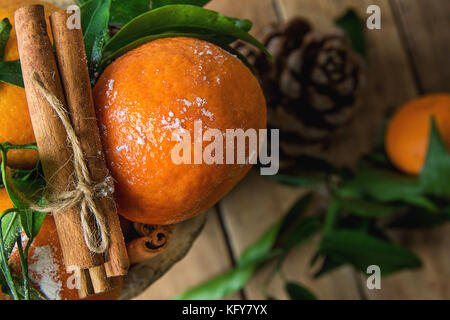 Vibrant Orange Tangerines on Branches Green Leaves Cinnamon Sticks tied with Twine Pine Cone Scattered on Wood Background. - Stock Photo
