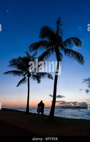 Silhouette of a couple watching a beautiful tropical Hawaiian Sunset over the pacific ocean in Magic Island on Oahu, - Stock Photo