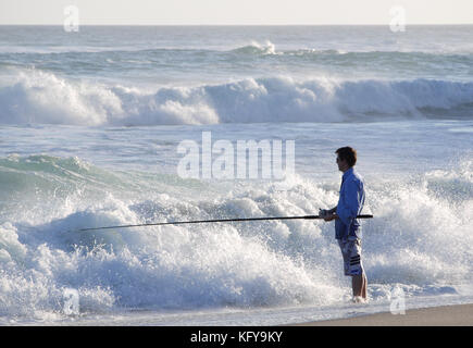 A lone fisherman standing in shallow water on Kangaroo Island in South Australia - Stock Photo