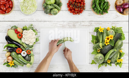 food top view hands cutting zucchini on white chopping board on kitchen wooden topwork with vegetables - Stock Photo