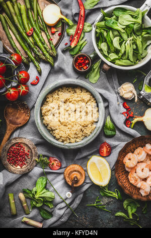 Top view of Healthy salad with asparagus and cooked quinoa seeds, preparation on rustic background with various - Stock Photo
