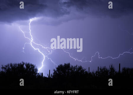 Lightning flashes from a thunderstorm in the Arizona desert. - Stock Photo