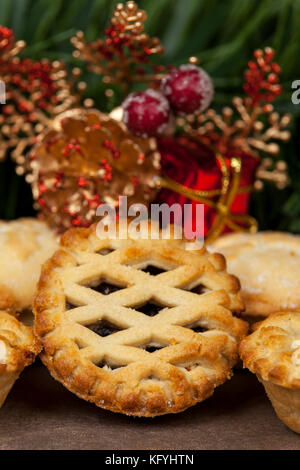 Close up of a lattice top mince pie with some christmas decorations in the background - Stock Photo