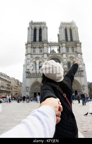 Asian thai woman lead someone by the hand and hold on walking at courtyard go to Cathedrale Notre-Dame de Paris - Stock Photo