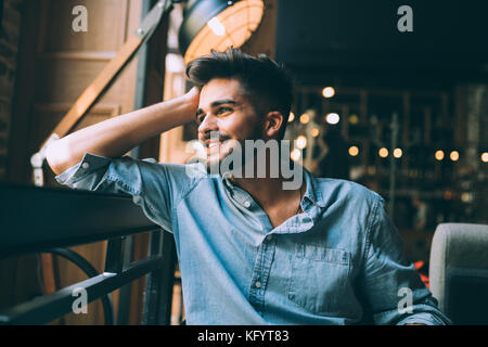 Portrait of young handsome man in blue shirt - Stock Photo