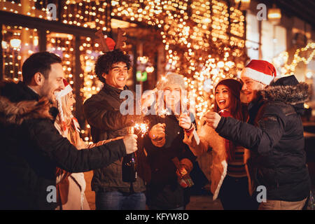 Group of happy friends having fun with sparklers on night Christmas party. - Stock Photo