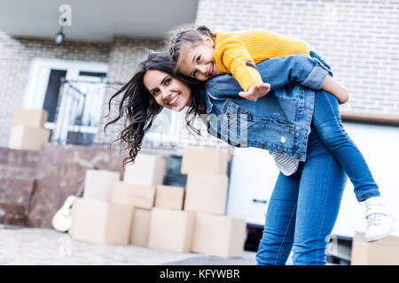 daughter piggyback riding mother - Stock Photo