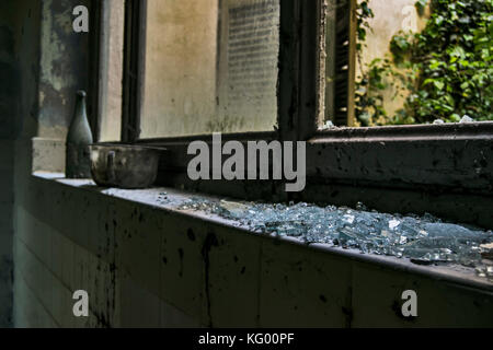 some broken pieces of glass on a wall in a room of an abandoned psychiatric hospital - Stock Photo
