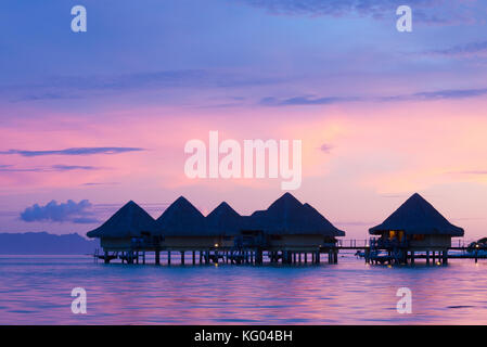 A pink sunset is reflected in the water below elevated bungalows in the Intercontinental Le Moana resort in Bora - Stock Photo
