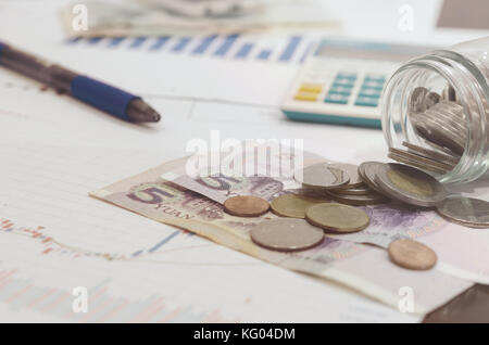 financial chart and coins on paper. - Stock Photo