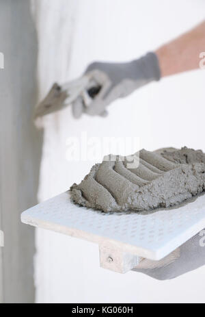 Close-up of construction worker holding a hand cement plaster - Stock Photo