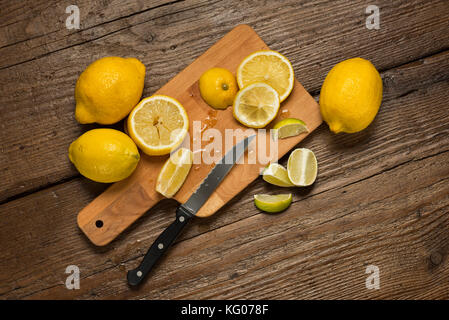 lemons, knife and lemon slices on chopping board, on wooden table. - Stock Photo
