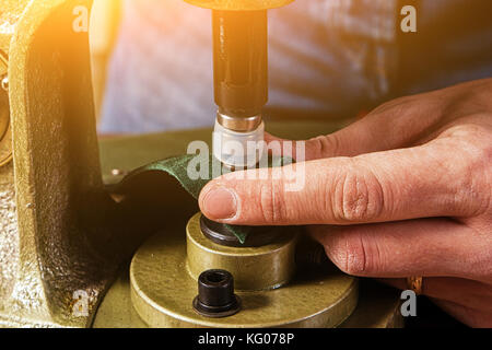 A close-up of a furrier flaps black metal buttons on a brown leather belt on an old hand riveter machine - Stock Photo