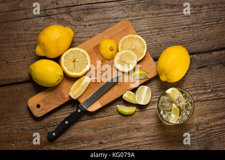 Lemons, knife and lemon slices on chopping board, with water glass on wooden table. - Stock Photo