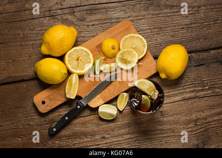 Lemons, knife and lemon slices on chopping board, with cocacola glass on wooden table. - Stock Photo