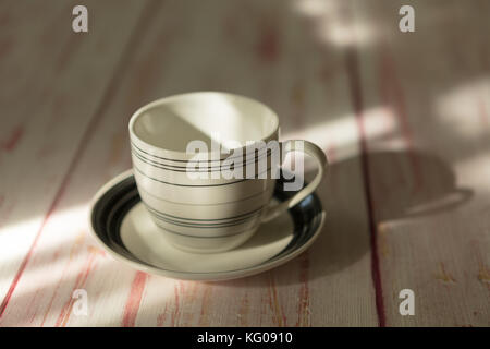 An empty  coffee or tea cup  place on old wooden table - Stock Photo