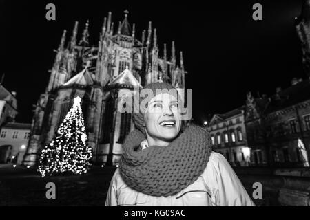 Magic on streets of the old town at Christmas. Portrait of smiling modern woman in red hat and scarf near Christmas - Stock Photo