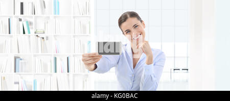 smiling woman showing smartphone in her hand on interior office background - Stock Photo