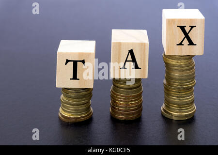 Tax Word on Wood Block on Top of Coins Stack With Black Background. - Stock Photo