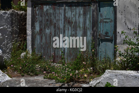 An old garage with weathered boards on a beautiful sunny day on the Greek island of Cephalonia - Stock Photo