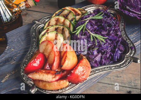 Braised red cabbage with grilled chunks of apples and onions, seasoning with lemon and olive oil on a beautiful - Stock Photo