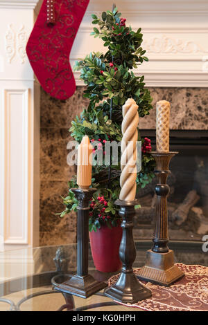 Living room decorated for Christmas with candlesticks, and a stocking hung at the fireplace mantle - Stock Photo